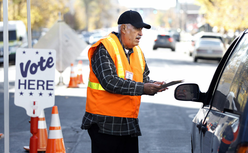 Denver County election judge Paul Aragon of Denver, Colorado collects ballots from a passing motorist outside the Denver Elections Division building October 22, 2012 in Denver, Colorado. Early voting began October 22 in Colorado is taking place in many battle ground states including Ohio, Wisconsin and Florida.