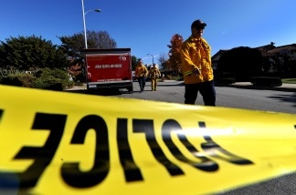 Firefighters walk past a police cordon at a residential area after a shooting incident in Covina, California.