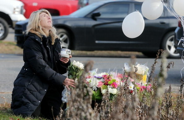 Andrea Jaeger places flowers and a candle at a makeshift memorial outside a firehouse which was used as a staging area for families following the mass shooting at Sandy Hook Elementary School on December 15, 2012 in Newtown, Connecticut.
