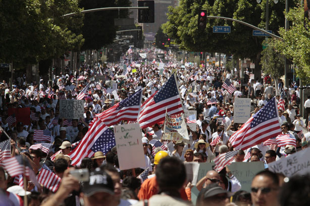 People march along Broadway in downtown Los Angeles during a rally for immigration law reform and to protest against Arizona's controversial new immigration law on Saturday, May 1, 2010.