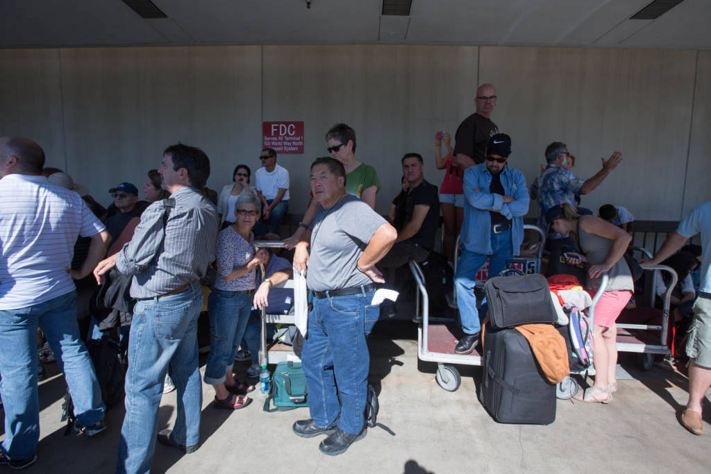 Passengers wait outside Terminal 1 at LAX after a shooting on November 1st, 2013.