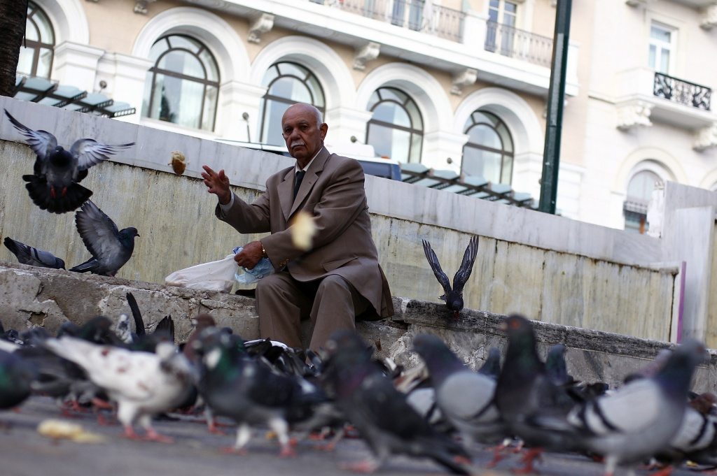 An elderly man feeds pigeons on Syntagma Square on November 3, 2011 in Athens, Greece. Greece stands on the brink of economice collapse as political disagreements continue concerning the financial aid package proposed by the EU.