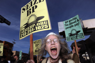 A protester shouts slogans against BP during a demonstration in front of the BP 'Green Curve' Station, in Los Angeles, California, on May 12, 2010.  (File photo Gabriel Bouys/AFP/Getty Images)