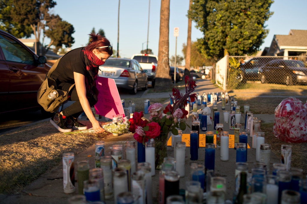 Marchers leave flowers and candles at a memorial on West 65th Street where Ford was fatally shot on Monday by Los Angeles police.