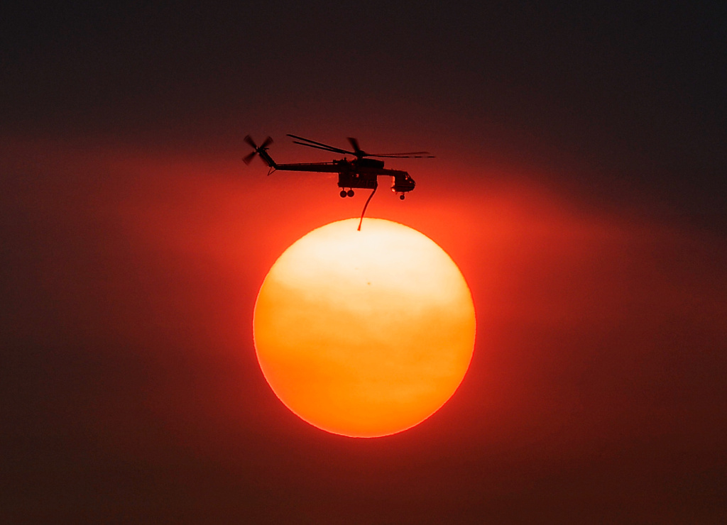 Smoke from the Mountain Fire obscures the sun as a fire fighting helicopter heads to fight the Mountain Fire after picking up water from Lake Hemet July 18, 2013 near Idyllwild, California.