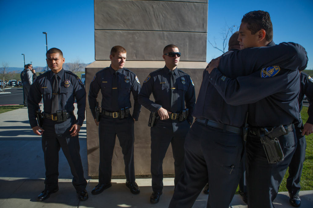 Riverside Police Officers console each other outside of Grove Community Church before Michael Crain's funeral on February 13th, 2013.