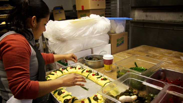 La Morenita baker Vianey Chavez stands over long lines of rolled dough in preparation for baking roscas.