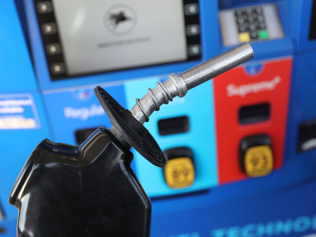A gas pump nozzle is seen at a gas station in Miami in 2018. Some activist shareholders are pushing companies to tie executive compensation to meeting climate targets.