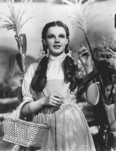This photo combo shows, at left, actress Judy Garland as Dorothy in a scene from
