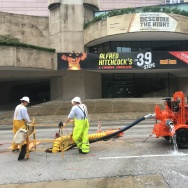 Crews pump water from the flooded basement of the Alley Theater in Houston's Theater District.