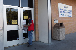A California Department of Motor Vehicles customer peers into the door of a closed DMV branch July 10, 2009 in Corte Madera, California. File photo.