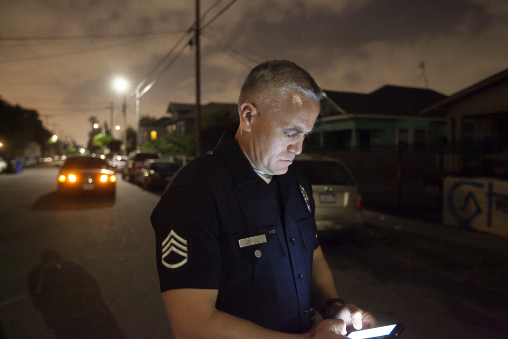 Los Angeles Police Sergeant Raul Jovel enters data in a field report after making a stop on E. 28th St. to check on some metro officers who were doing a search at a home on Tuesday, May 12, 2015 in Los Angeles, Calif.