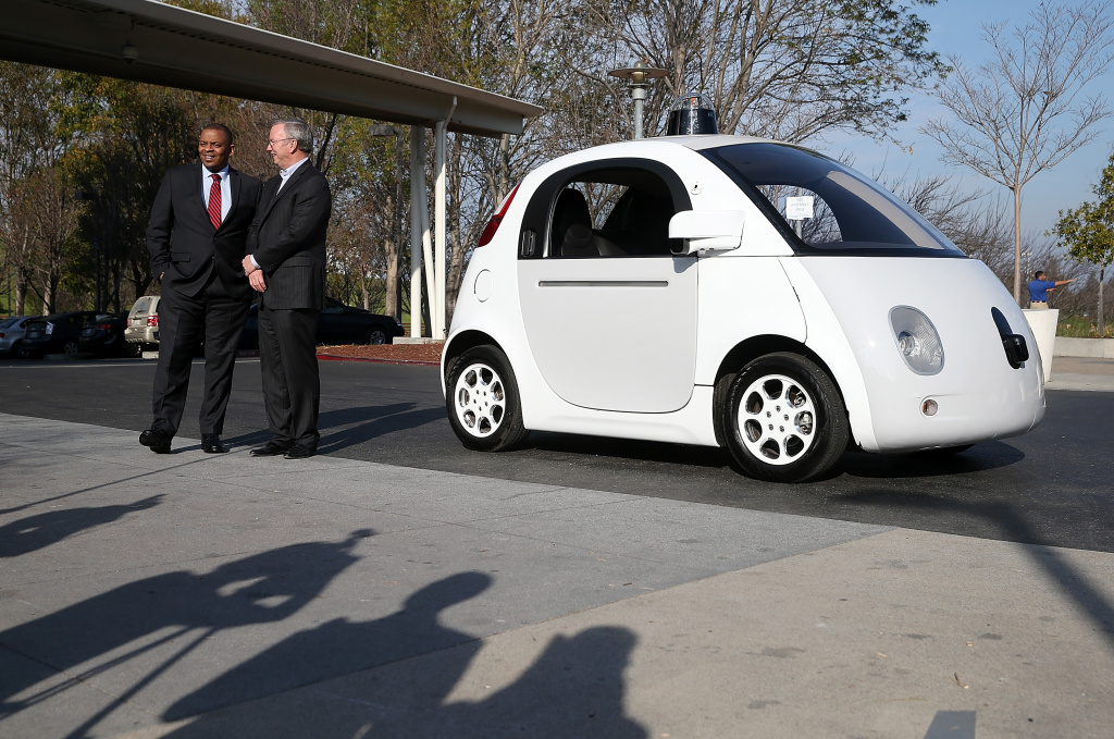 U.S. Transportation Secretary Anthony Foxx (L) and Google Chairman Eric Schmidt (R) stand next to a Google self-driving car at the Google headquarters on February 2, 2015 in Mountain View, California. On Wednesday, the state unveiled precedent-setting draft rules that would slow the public's access to self-driving cars until regulators are confident the technology is safe.
