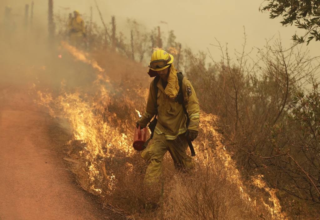 A Sonoma City firefighter walks in front of flames during a backburn operation Friday, Oct. 13, 2017, in Glen Ellen, California.