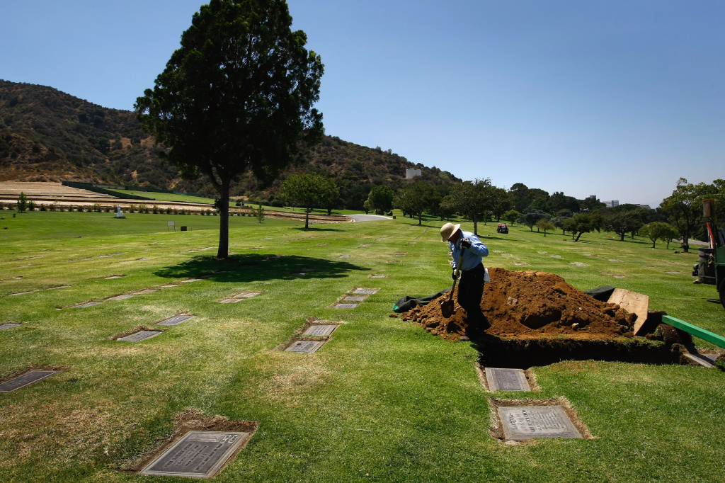 A grave digger prepares for a funeral of an unidentified person at Forest Lawn Memorial-Parks and Mortuaries Mortuary in Los Angeles, California.