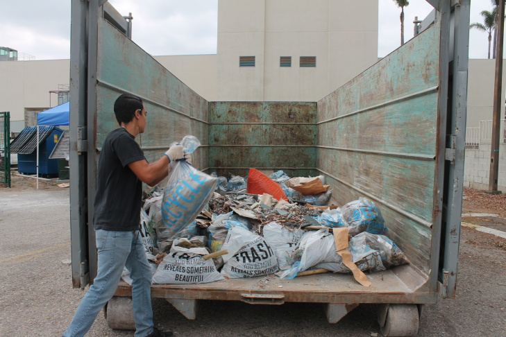 Anthony Bernal, 16, tosses trash from Compton Creek into a dumpster for Coastal Cleanup Day on Sept. 21, 2013.