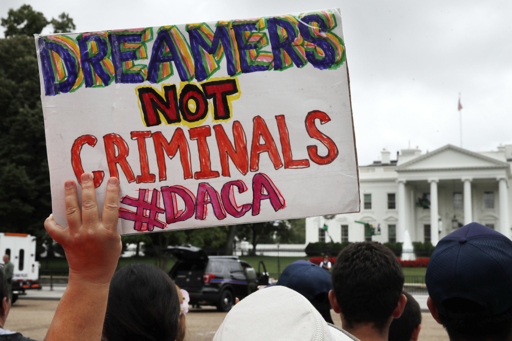 FILE- In this Aug. 15, 2017, file photo, a woman holds up a signs in support of the Obama administration program known as Deferred Action for Childhood Arrivals, or DACA, during an immigration reform rally at the White House in Washington.