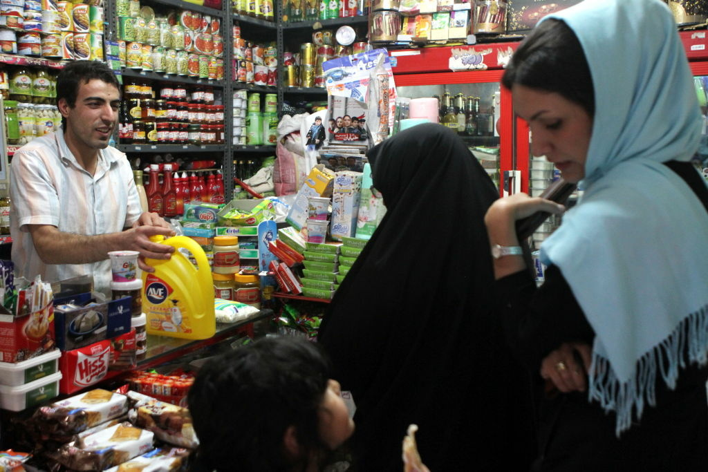 A woman makes a purchase at a convenience store in Iran. How have sanctions imposed on Iran by the U.S. and the E.U. effected the country's economy?