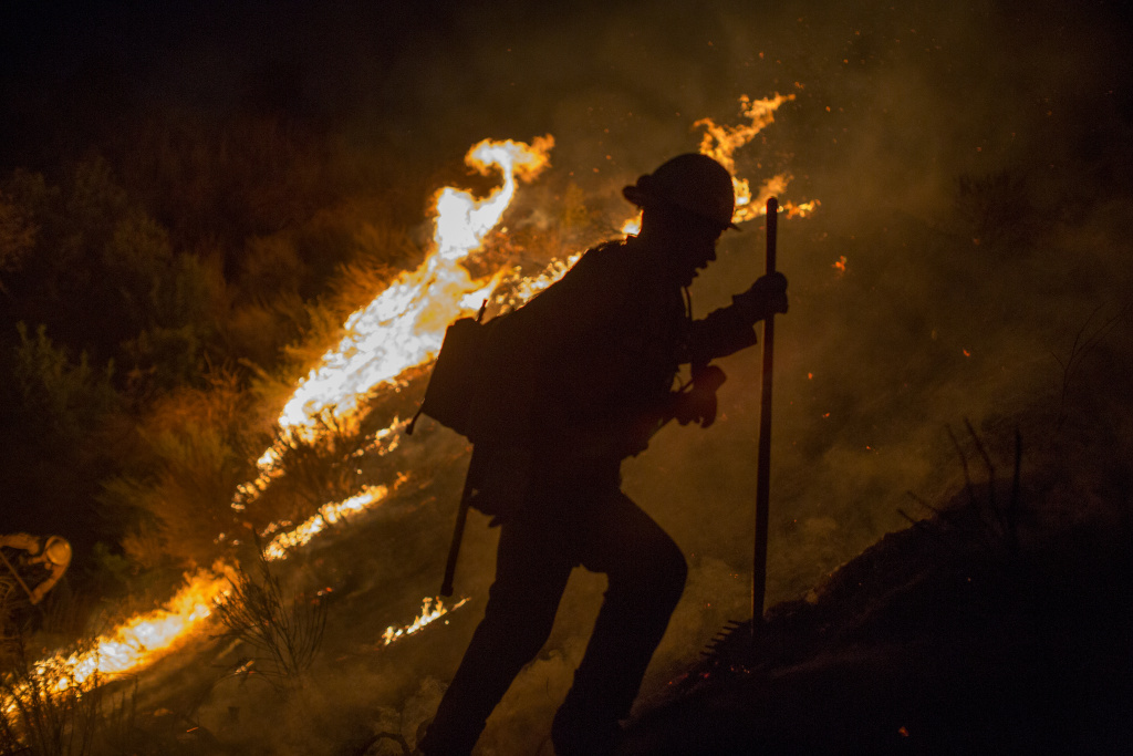 BURBANK, CA - SEPTEMBER 02: A firefighter climbs a burning hillside after having fallen into a hole fighting while the La Tuna Fire on September 2, 2017 near Burbank, California. Los Angeles Mayor Eric Garcetti said at a news conference that officials believe the fire, which is at 5,000 acres and growing, is the largest fire ever in L.A. People have been evacuated from hundreds of homes in Sun Valley, Burbank and Glendale. About 100 Los Angles firefighters are expected to return soon from Texas, where they've been helping survivors from Hurricane Harvey.    (Photo by David McNew/Getty Images)