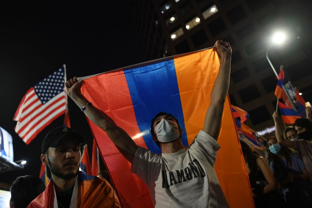 A man holds up an Armenian flag during a protest organized by the Armenian Youth Federation outside the Azerbaijani Consulate General in Los Angeles.