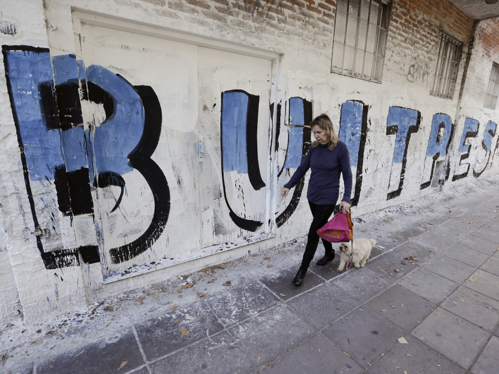 A woman in Buenos Aires walks with her dog past a mural that reads