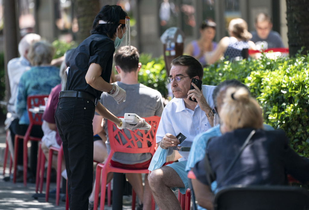 A waiter at a restaurant wears a protective face mask as provide a contactless paying system for customers dining outdoors amid the coronavirus pandemic on June 12, 2020 in Bethesda, Maryland.