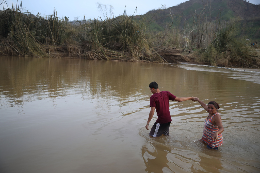 Hector Ojeda and Sonia Robles cross a river on foot after the bridge was washed away when Hurricane Maria passed through on September 27, 2017 in Morovis, Puerto Rico.