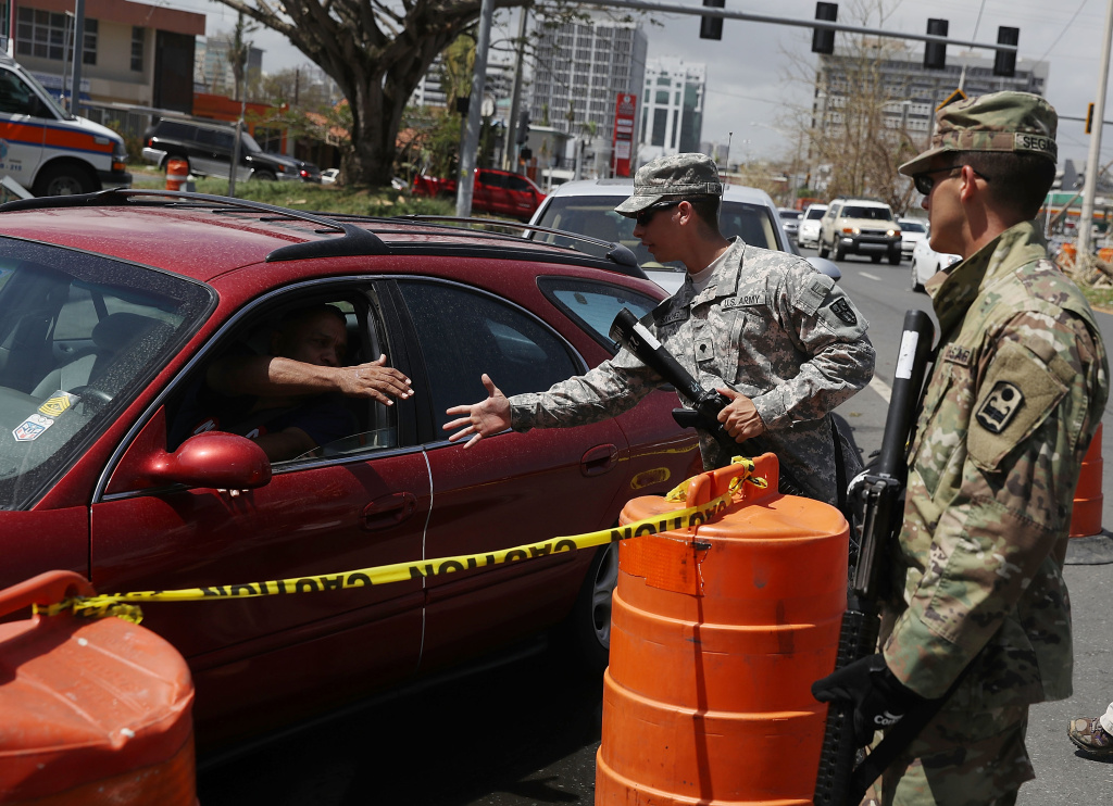 Puerto Rican National Guard Specialists David Sanchez and Ismael Segarra stand guard near a line of vehicles waiting for gas as they deal with the aftermath of Hurricane Maria in San Juan, Puerto Rico.