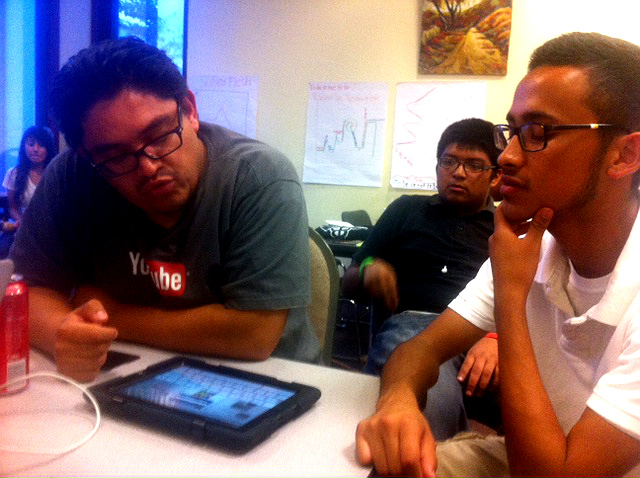 Developer Oscar Menjivar sits with student Jesus Vargas, checking out the Pearson education software loaded onto every L.A. Unified iPad.