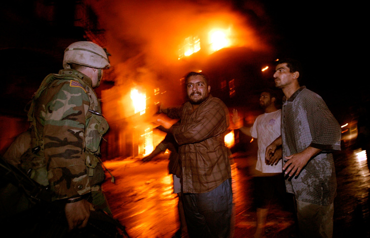 Residents and workers in central Baghdad plead with a U.S. soldier to bring water to a fire that erupted after a explosion ripped through a building in the book market area of the city Thursday October 30, 2003.