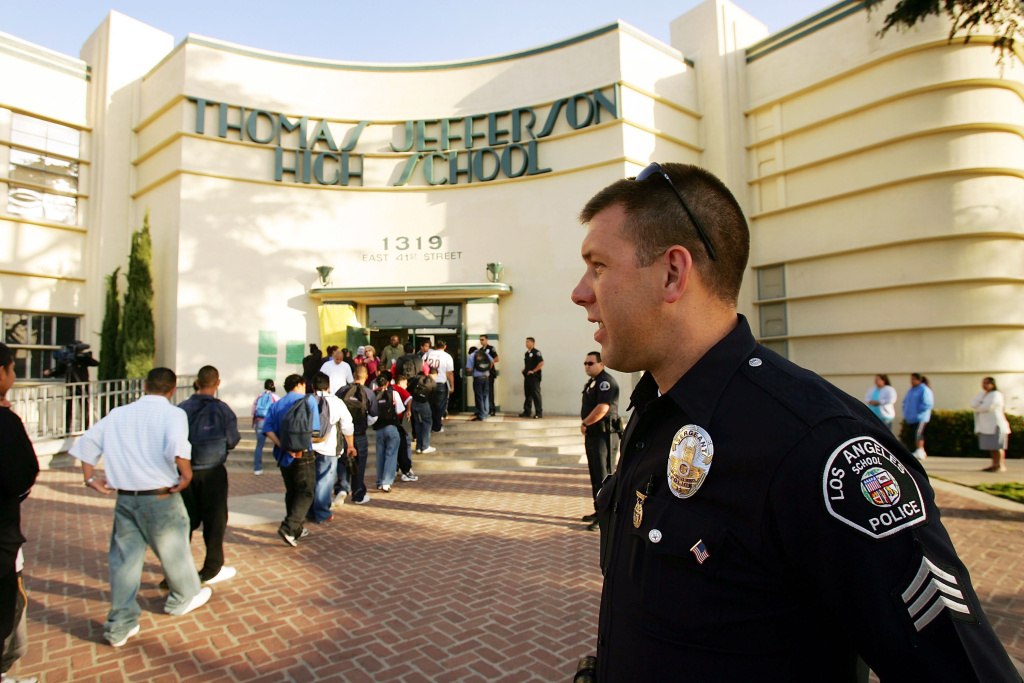 Los Angeles School Police Sgt. Robert Carlborn watches over students lining up to pass through a security check point.