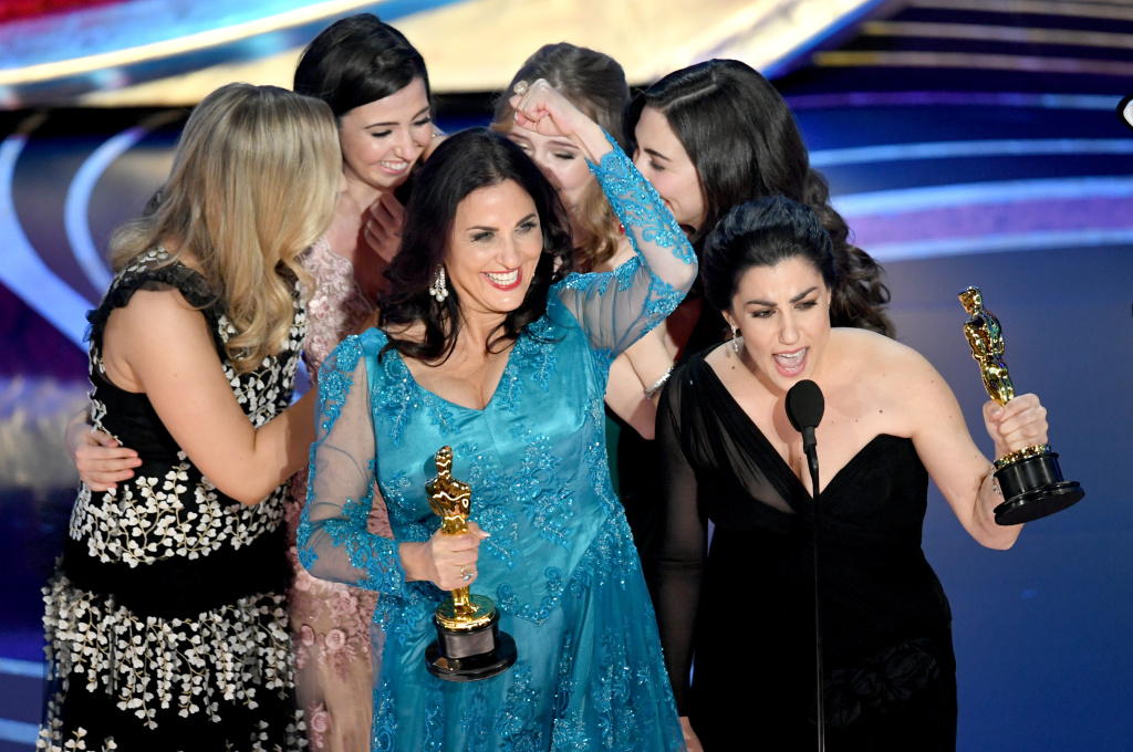 Producer Melissa Berton (center) and director Rayka Zehtabchi (right) accept an Oscar for their documentary 'Period. End of Sentence.'