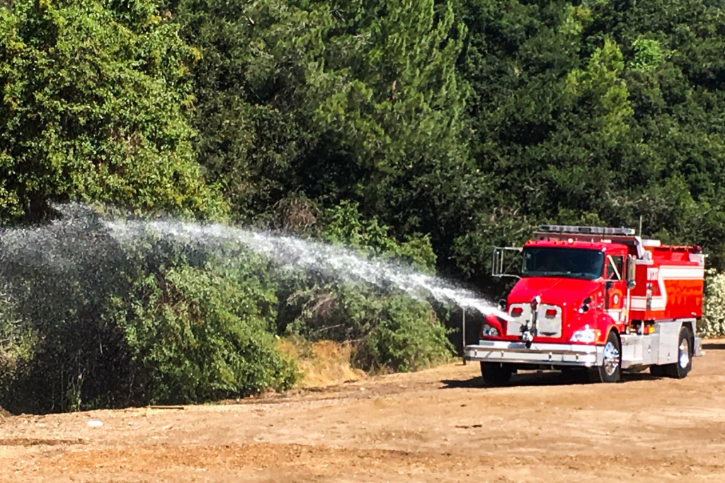 A Pasadena Fire engine sprays fire retardant on shrubbery near the Rose Bowl.