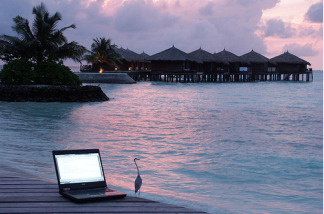 Laptop sits on a pier by the shore in the Maldives.