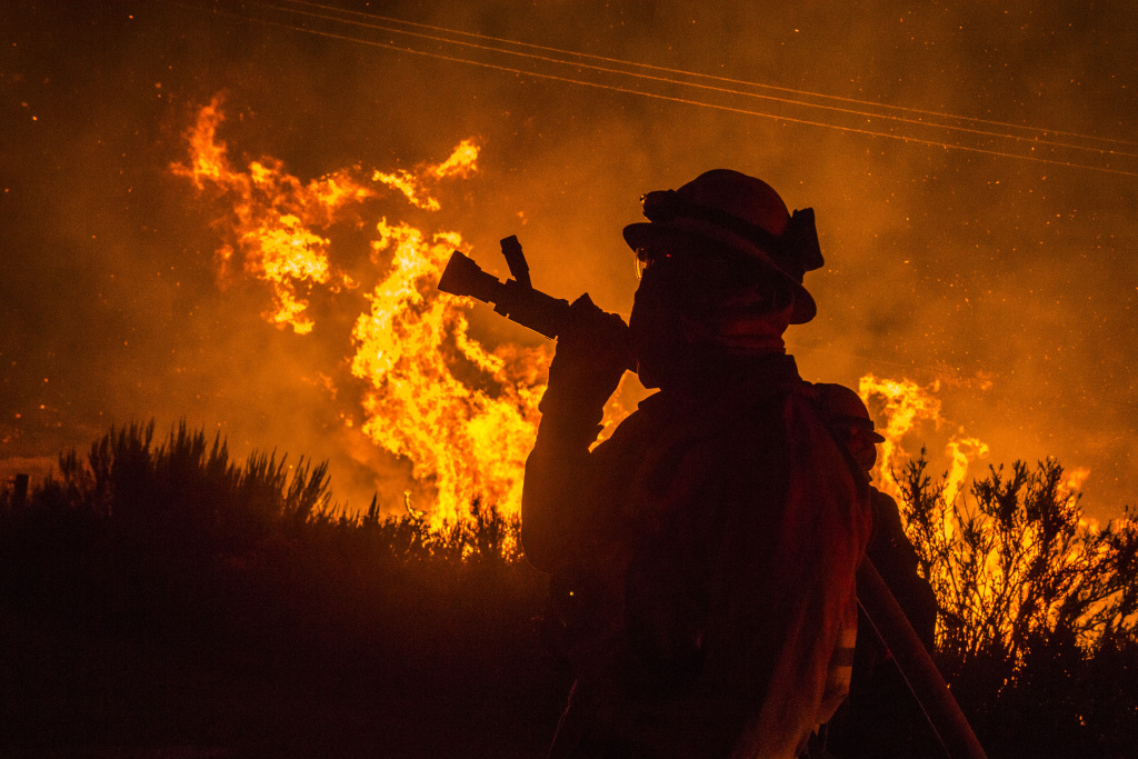 Firefighters try to prevent the Pilot Fire from burning over Highway 173 Sunday night. The Pilot Fire burns in the San Bernardino National Forest Sunday afternoon Aug. 7, 2016.
