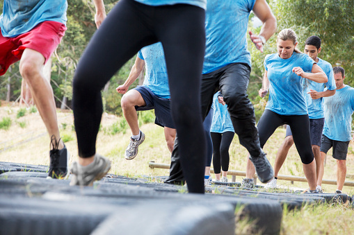 Jumping tires on boot camp obstacle course
