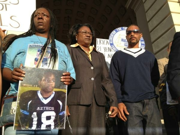 The family of Kendrec McDade and attorney Caree Harper at an earlier rally at Pasadena City Hall. A relative is holding a photo of McDade in a football uniform.