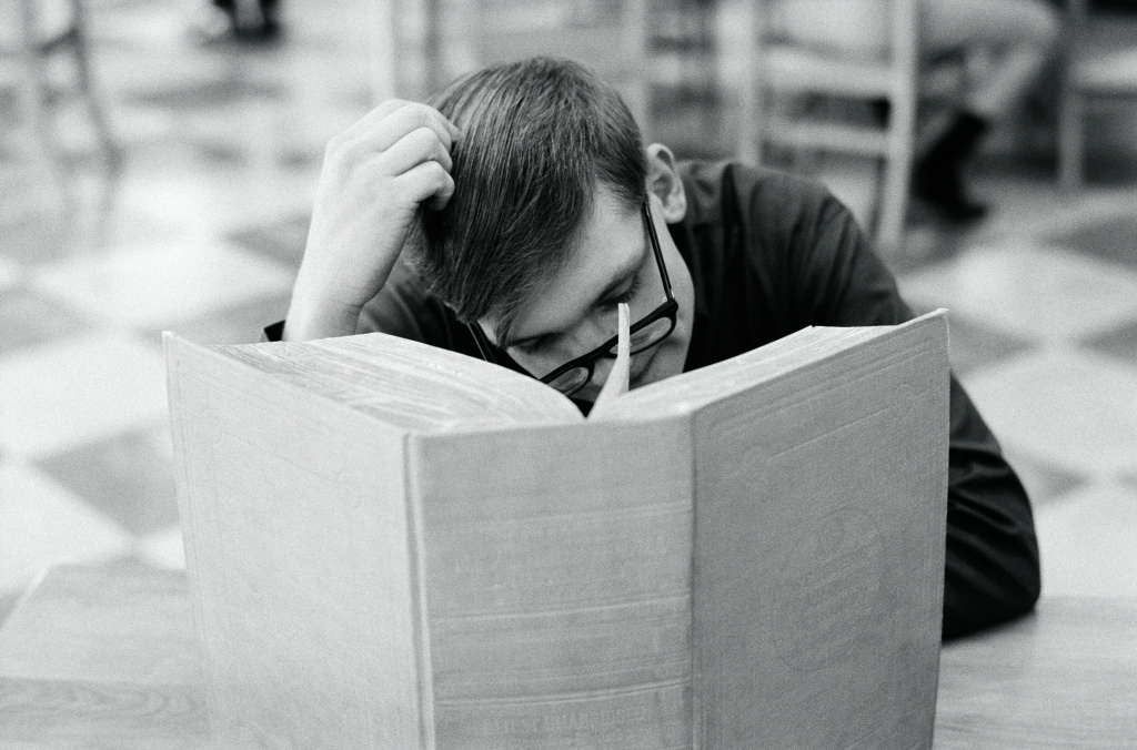 CIRCA 1950s: Man sitting at library table, scratching head, with large book open in front of him