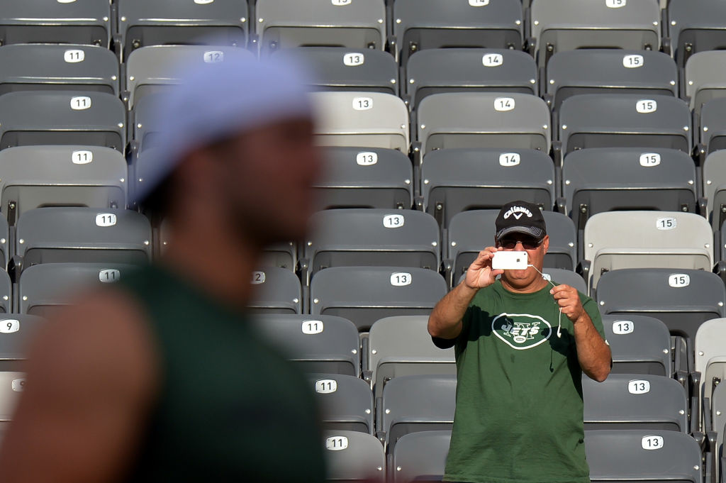 A fan uses a smartphone to photograph Tim Tebow #15 of the New York Jets as he walks across the field before the game against the New York Giants at MetLife Stadium on August 18, 2012 in East Rutherford, New Jersey.