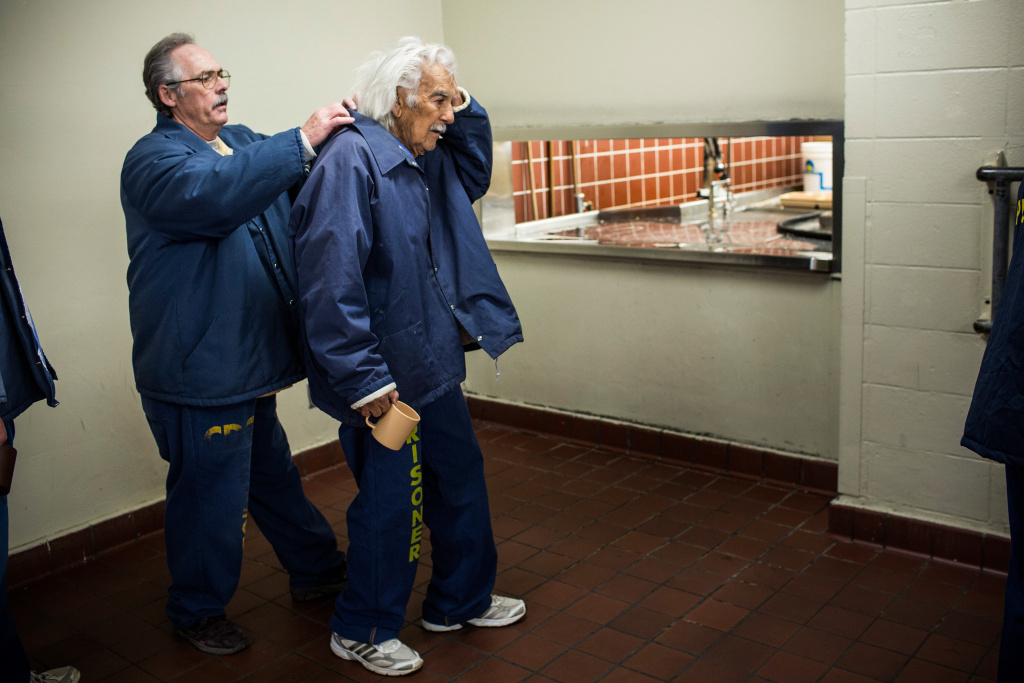 Anthony Alvarez (R), age 82, waits in line for breakfast while being assisted by Phillip Burdick, a fellow prisoner and member of the Gold Coats program at California Men's Colony prison on December 19, 2013 in San Luis Obispo, California.  The Gold Coats program is a volunteer care program where healthy prisoners volunteer to take care of elderly prisoners who either need general assistance with mobility and every day life or who also struggle with Alzheimer's and dementia.