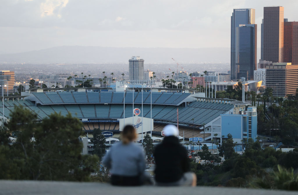People sit on a hill overlooking Dodger Stadium on what was supposed to be Major League Baseball's opening day, now postponed due to the coronavirus, on March 26, 2020 in Los Angeles, California.