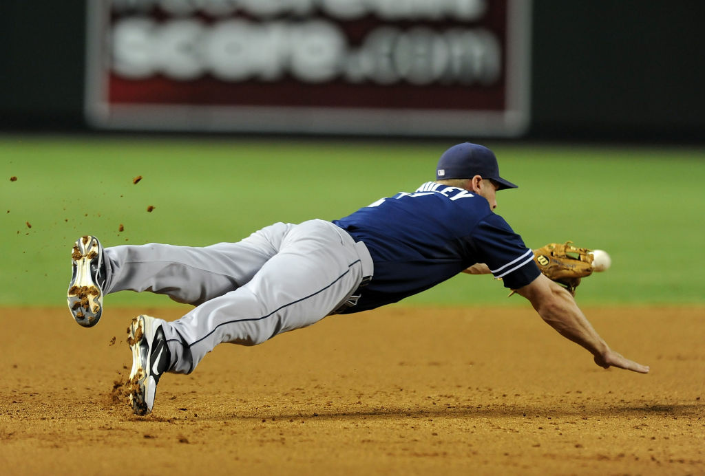 Chase Headley of the San Diego Padres dives for a ground ball against the Arizona Diamondbacks. The Padres have officially changed hands, for $800 million.