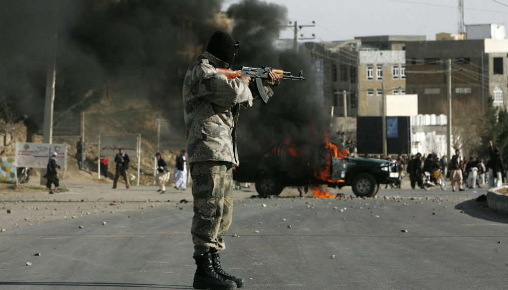 An Afghan policeman aims at protesters by a burning police truck set alight during an anti-U.S. demonstration