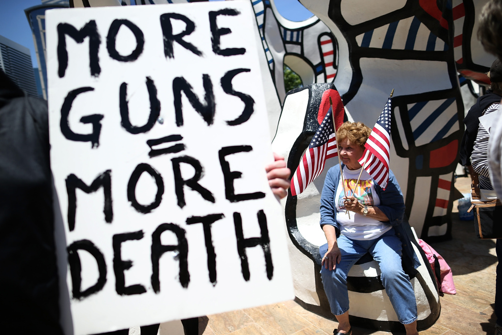 HOUSTON, TX - MAY 04:  A protestor holds American flags during a demonstration in favor of gun regulation outside of the 2013 NRA Annual Meeting and Exhibits at the George R. Brown Convention Center on May 4, 2013 in Houston, Texas.  More than 70,000 peope are expected to attend the NRA's 3-day annual meeting that features nearly 550 exhibitors, gun trade show and a political rally. The Show runs from May 3-5.  (Photo by Justin Sullivan/Getty Images)