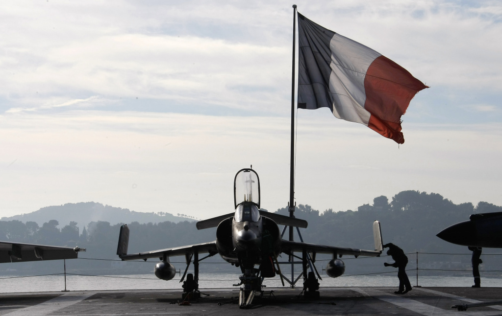 A French sailor checks a Super-Etendard fighter jet on the deck of France's nuclear-powered aircraft carrier Charles de Gaulle before it leaves its home port of Toulon on Wednesday. France has deployed its aircraft carrier in the eastern Mediterranean to help fight ISIS.