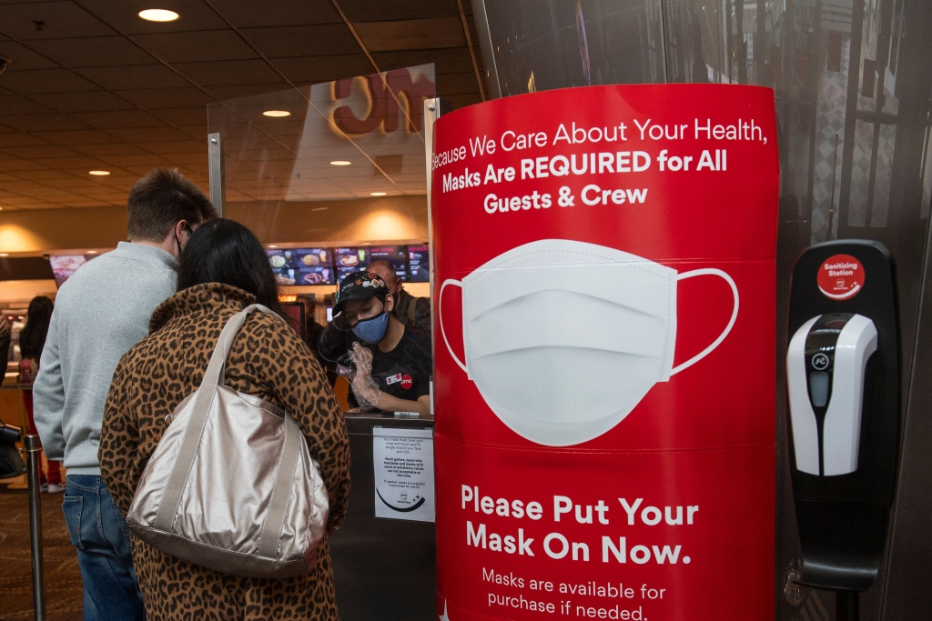 A sign asking people to wear a mask is displayed as moviegoers buy tickets at the AMC Burbank theatre on reopening day in Burbank, California, March 15, 2021.