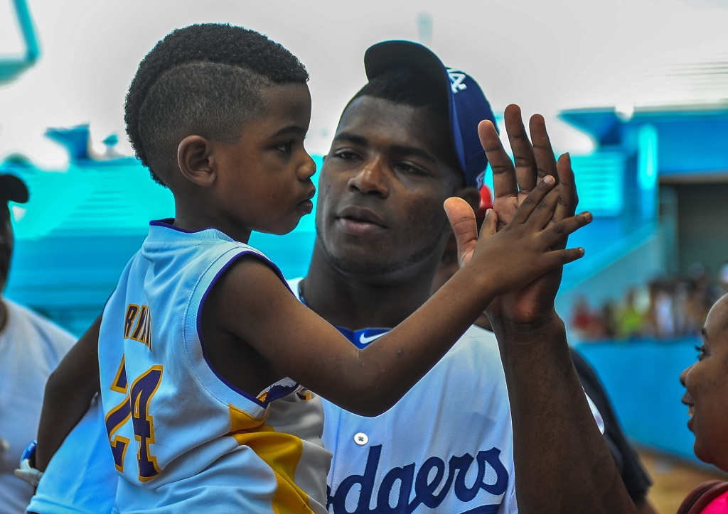 Yasiel Puig holds his nephew during a children baseball training session in Havana, Cuba on December 16, 2015.