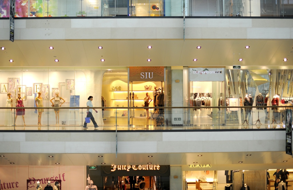 A shop employee (C) walks past boutiques at a shopping mall in Beijing on September 11, 2011.