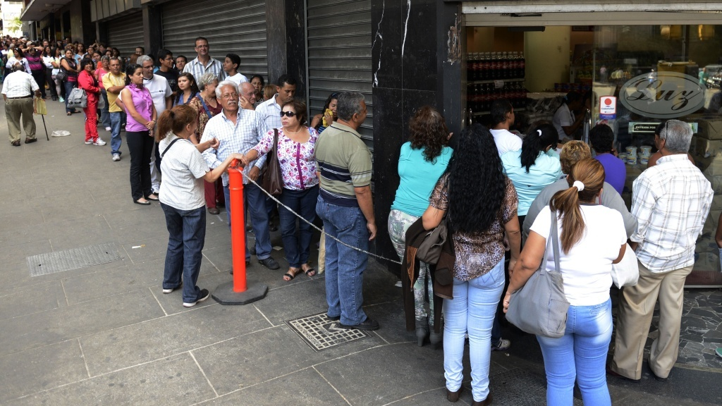 People line up to buy goods at a store in Caracas, Venezuela.