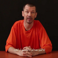 In this still image taken from the first video released by Al-Furqan, the media arm of the Islamic State militant group, captive British journalist John Cantlie speaks into the camera.